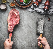 Male hands of butcher or cook holding tomahawk beef steak and meat cleaver on dark rustic kitchen table background with cooking i Royalty Free Stock Photos