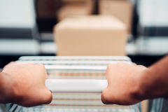 Male hands with cargo trolley, cargo delivery. Male hands with cargo trolley. Truck with parcels on background. Distribution business. Cargo delivery. Empty stock photos