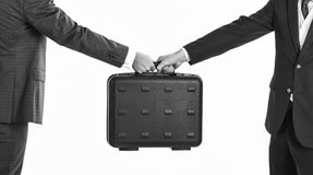 Male hands carry briefcase for exchange. Male hands in suits hold black briefcase. Business exchange concept. Handover of case in hands of business partners Stock Photography