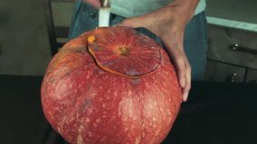 Male hands carves pumpkin, take off a top. Halloween theme, jack o lantern. Close up shot stock footage