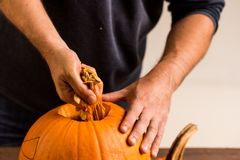 Male hands carving pumpkin taking out seeds Stock Photography