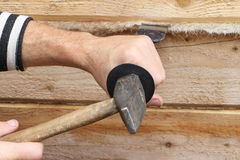 Male hands caulk a house wall from a bar Royalty Free Stock Photos