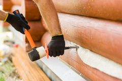 Male hands caulk log walls Stock Images