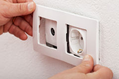 Male hands changing an electical wall outlet Stock Photography