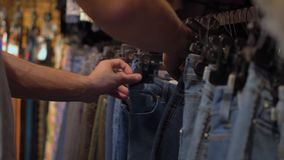 Male hands choosing chinos in the clothing store Close-up with changing focus. Shopping stock footage