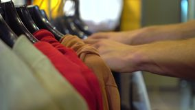Male hands choosing jacket in the clothing store Close-up with changing focus. Shopping stock video