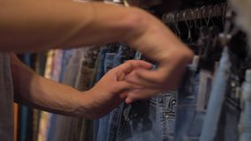 Male hands choosing jeans in the clothing store Close-up with changing focus. Shopping stock footage