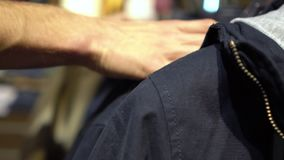 Male hands choosing new clothes in the clothing store Close-up with changing focus. Shopping stock footage