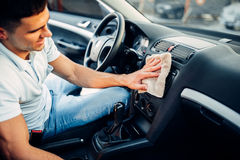 Male hands cleans auto, car dashboard polishing. On carwash station. Man rubbing vehicle torpedo with polish Royalty Free Stock Photo