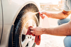 Male hands cleans disk with car rim cleaner Stock Photo