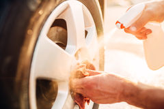 Male hands cleans disk with car rim cleaner Royalty Free Stock Image