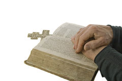 Male hands closed in prayer on an open bible. Isolated over white Stock Images