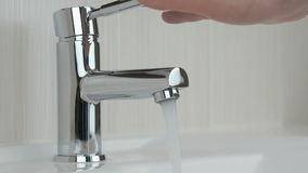 Male hands closing chrome-plated tap of water stock video