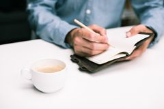 Male hands with coffee cup writing in diary. Cropped view of male hands with coffee cup writing in diary Stock Photo