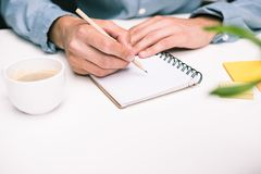Male hands with coffee cup writing in diary. Cropped view of male hands with coffee cup writing in diary Royalty Free Stock Images