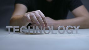 Male hands composition word technology from white letters on gray background. Concept introduction technologies in modern business and life. Introduction new stock footage