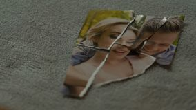 Male hands connecting tearing pieces of photo with his girlfriend, yearning stock video