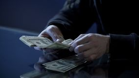 Male hands counting dollars, black salary, money laundering, illegal business stock images