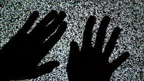 Male hands crawling up the TV screen with static television noise as background. 1920x1080 full hd footage stock footage