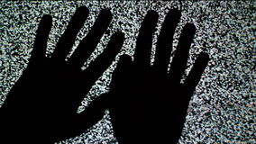 Male hands crawling up the TV screen with static television noise as background. stock video