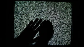 Male hands crawling up the TV screen with static television noise as background. stock video footage