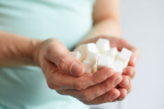 Male hands with cubes of white sugar Royalty Free Stock Images
