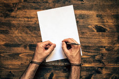 Male hands cuffed signing confession, top view Royalty Free Stock Photos