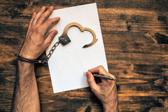 Male hands cuffed signing confession, top view Stock Images