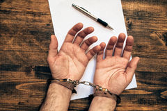 Male hands cuffed, top view of police investigator desk Royalty Free Stock Photos