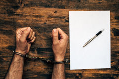 Male hands cuffed, top view of police investigator desk Stock Image