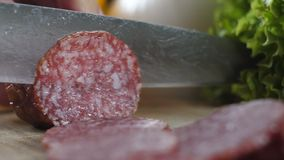 Male hands cut salami into thin slices. Close up stock video
