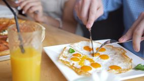 Male hands cuts a tasty and useful fried eggs with a knife and fork in restaurant. Close up stock video footage