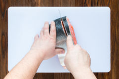 Male hands cutting piece of salmon. On a white cutting board on wooden background, top view Royalty Free Stock Image