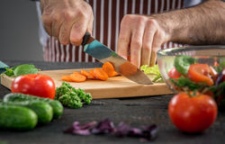 Male hands cutting vegetables for salad. Close up on male hands cutting carrot, making salad. Chief cutting vegetables. Healthy lifestyle, diet food Stock Images