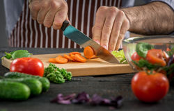 Male hands cutting vegetables for salad. Close up on male hands cutting carrot, making salad. Chief cutting vegetables. Healthy lifestyle, diet food Royalty Free Stock Photography