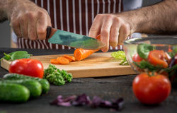 Male hands cutting vegetables for salad. Close up on male hands cutting carrot, making salad. Chief cutting vegetables. Healthy lifestyle, diet food Stock Photography