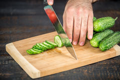 Male hands cutting vegetables for salad. Close up on male hands cutting cucumber, making salad. Chief cutting vegetables. Healthy lifestyle, diet food Royalty Free Stock Photos