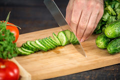 Male hands cutting vegetables for salad. Close up on male hands cutting cucumber, making salad. Chief cutting vegetables. Healthy lifestyle, diet food Royalty Free Stock Image