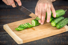 Male hands cutting vegetables for salad. Close up on male hands cutting cucumber, making salad. Chief cutting vegetables. Healthy lifestyle, diet food Stock Image