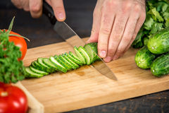 Male hands cutting vegetables for salad. Close up on male hands cutting cucumber, making salad. Chief cutting vegetables. Healthy lifestyle, diet food Royalty Free Stock Photo