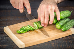 Male hands cutting vegetables for salad. Close up on male hands cutting cucumber, making salad. Chief cutting vegetables. Healthy lifestyle, diet food Stock Photography