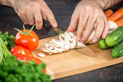 Male hands cutting vegetables for salad. Close up on male hands cutting tomato, making salad. Chief cutting vegetables. Healthy lifestyle, diet food Royalty Free Stock Photo