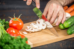 Male hands cutting vegetables for salad. Close up on male hands cutting tomato, making salad. Chief cutting vegetables. Healthy lifestyle, diet food Royalty Free Stock Image