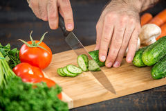 Male hands cutting vegetables for salad. Close up on male hands cutting tomato, making salad. Chief cutting vegetables. Healthy lifestyle, diet food Royalty Free Stock Photography