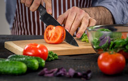 Male hands cutting vegetables for salad. Close up on male hands cutting tomato, making salad. Chief cutting vegetables. Healthy lifestyle, diet food Royalty Free Stock Images