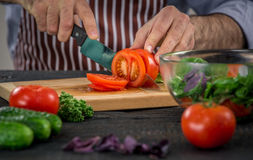 Male hands cutting vegetables for salad. Close up on male hands cutting tomato, making salad. Chief cutting vegetables. Healthy lifestyle, diet food Stock Image