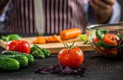 Male hands cutting vegetables for salad. Close up tomato, making salad. Chief cutting vegetables. Healthy lifestyle, diet food Royalty Free Stock Photos