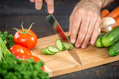 Male hands cutting vegetables for salad. Close up on male hands cutting tomato, making salad. Chief cutting vegetables. Healthy lifestyle, diet food Stock Photo