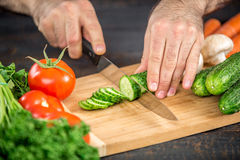 Male hands cutting vegetables for salad. Close up on male hands cutting tomato, making salad. Chief cutting vegetables. Healthy lifestyle, diet food Royalty Free Stock Photos