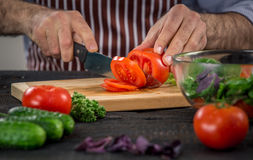 Male hands cutting vegetables for salad. Close up on male hands cutting tomato, making salad. Chief cutting vegetables. Healthy lifestyle, diet food Stock Photography